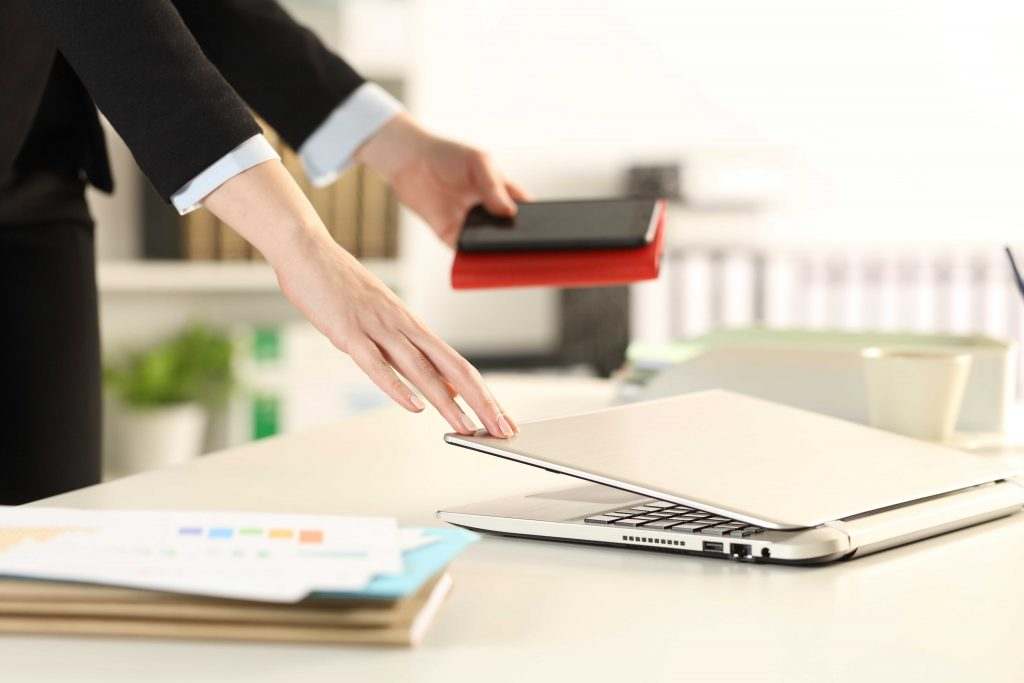 Executive hands leaving office closing laptop